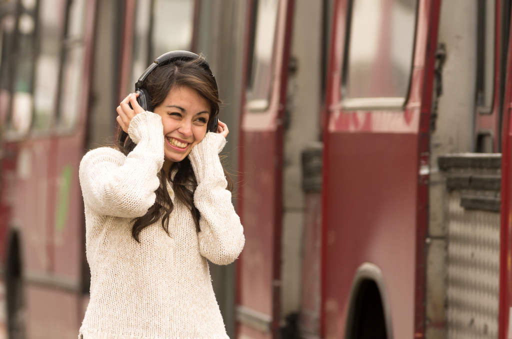 woman wearing noise cancelling headphones amidst heavy traffic